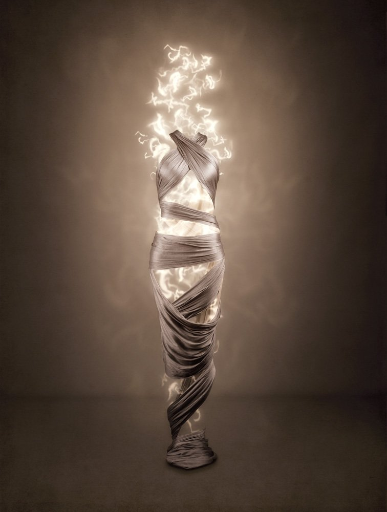 female form depicted in draped silk with light glowing from within